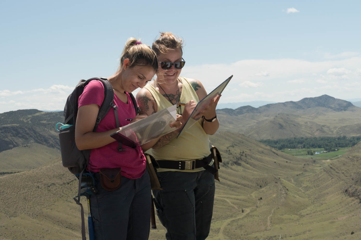 Two students look at their equipment as they map an outcrop.