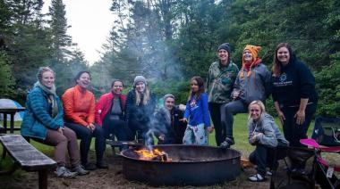 Members of the IgDEAS group sit around a campfire.