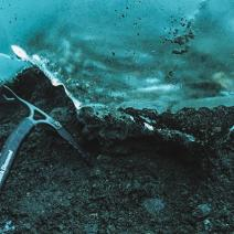 UO postdoctoral researcher Colin Meyer reaches with an ice axe, Alaska (photo by Kiya Riverman).