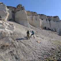 Geologists examine a rocky outcrop.